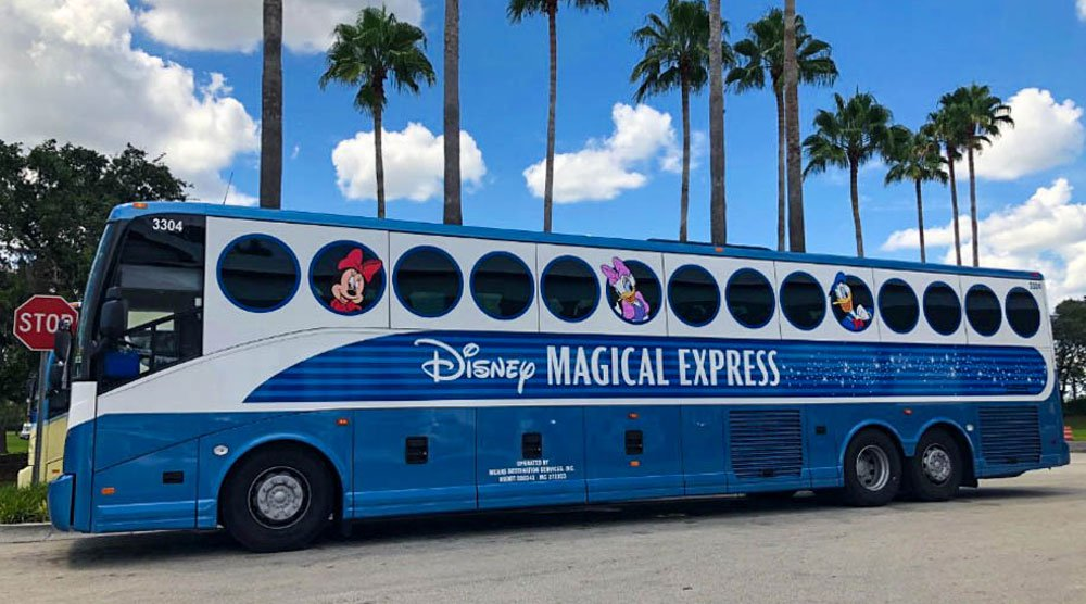 Photo of blue and white Disney Magical Express bus. Minnie Mouse, Daisy Duck and Donal Duck peek out from the round windows.